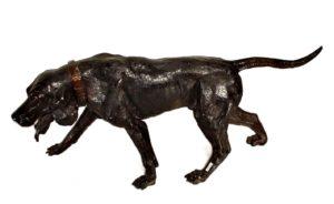 Perro de bronce pavonado con correa y mirando al suelo