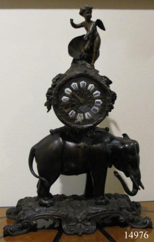 Reloj de sobremesa de bronce pavonado: Elefante sobre base de bronce, reloj circular y ángel en parte superior. S. XIX