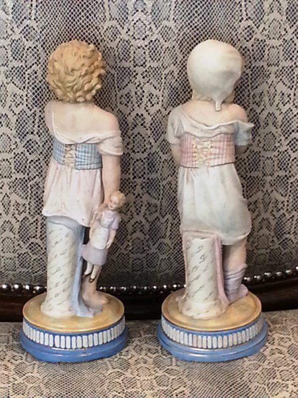 Pareja Figuras de porcelana Biscuit: Niña con muñeca en la mano y Niña con sombrero. S. XIX.